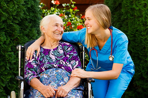 An image of an elderly person in a wheelchair with a care worker having a good time