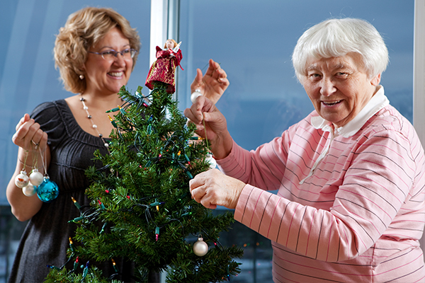 An image of an elderly person and a care worker decorating a Christmas tree