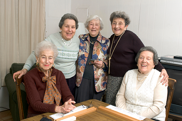 An image of five elderly people playing scrabble