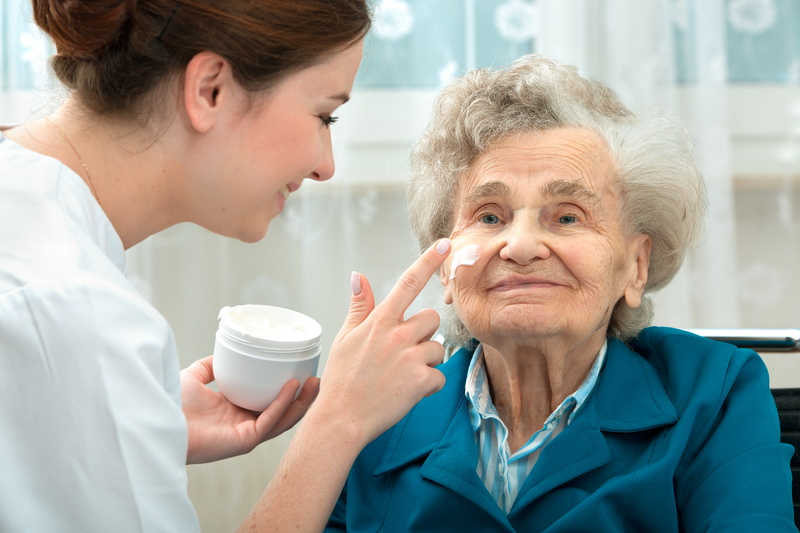 An image of a care worker applying moistener to an elderly persons face