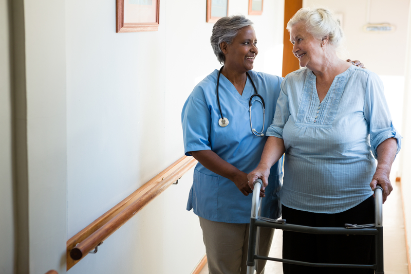 An image of a care worker helping an elderly person walk